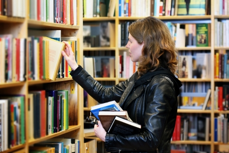 Student in a library choosing a book Stock Photo - 17189137