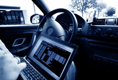 Man stealing data from a laptop sitting in a car photo