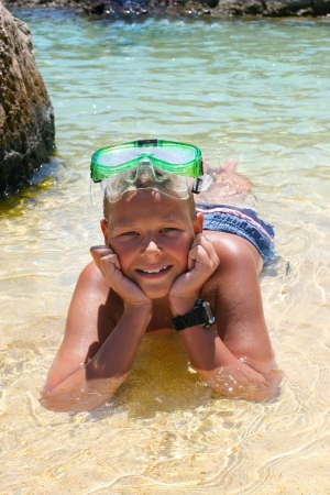 Kid in a diving mask having summer fun in the water photo