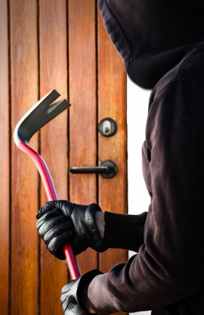 doorlock: Burglar hand holding crowbar  Stock Photo