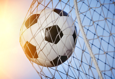 Soccer ball kicked into the back of a goal Stock Photo