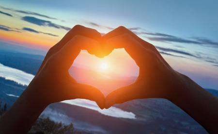 Mains, forme coeur, plage, contre, lever soleil, sur, montagnes Banque d'images - 68217588