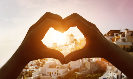 Silhouette hand in heart shape with sunrise in the middle and  Santorini
