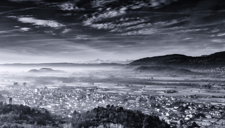 the town of Montalto Dora dipped in morning mists with the Alps and the background monviso Stock Photo