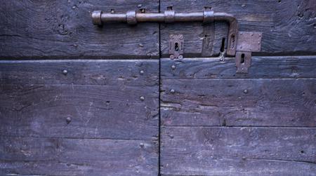 ancient wooden door with metal latch and lock Imagens