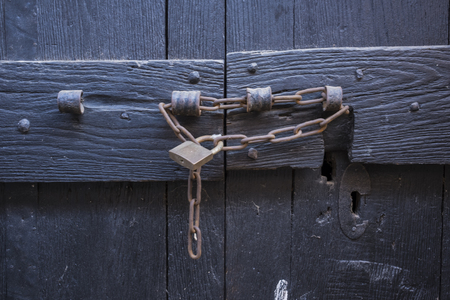 detail of antique wooden door with rusty lock and chain