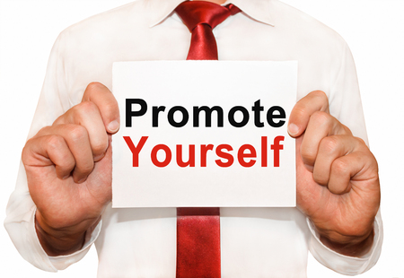 promote: Man holding a card with a text Promote Yourself