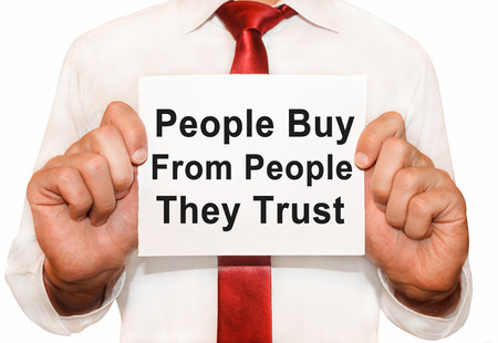 trust people: Man holding a card with a text People Buy From People They Trust.