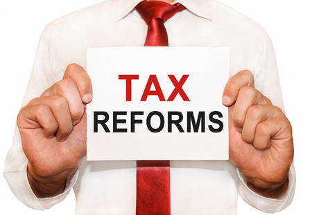 Man holding a card with a text Tax Reforms.