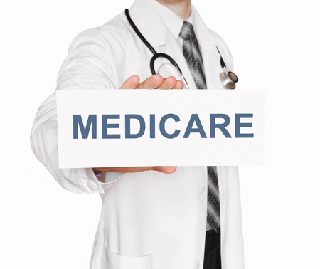 Doctor holding a card with Medicare, Medical concept Stock Photo