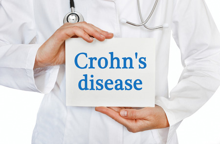 Crohns disease card in hands of Medical Doctor Stock Photo