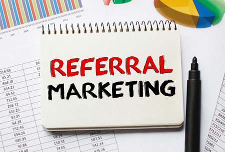 referidos: Notebook with Toolls and Notes about Referral Marketing Foto de archivo