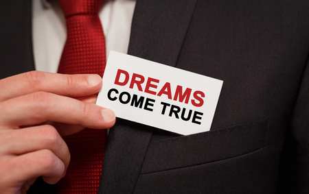 Businessman putting a card with text Dreams Come True in the pocket Stock Photo