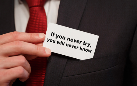Businessman putting a card with text If you never try, you will never know in the pocket Stock Photo