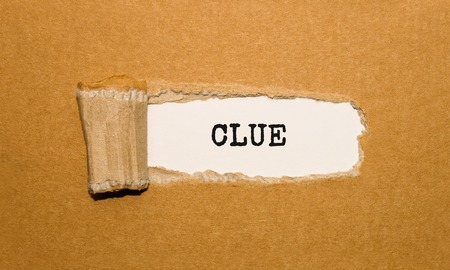 The text CLUE appearing behind torn brown paper