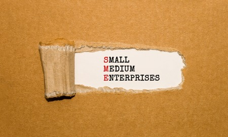 The text SME SMALL MEDIUM ENTERPRISES appearing behind torn brown paper Stock Photo