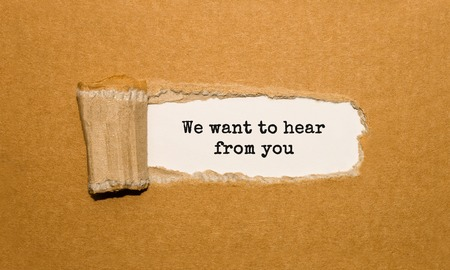 The text We want to hear from you appearing behind torn brown paper Standard-Bild