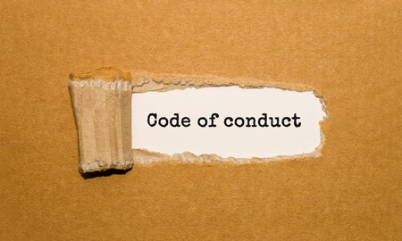 The text Code of conduct appearing behind torn brown paper