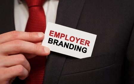 ポケットに雇用ブランディング テキストでカードを置くビジネスマン 写真素材