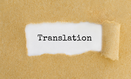 Text Translation appearing behind ripped brown paper. Stok Fotoğraf