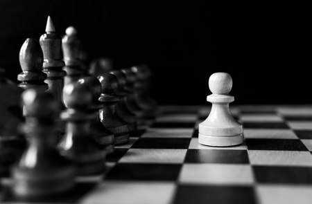 One pawn staying against full set of chess pieces. Business and strategy concept