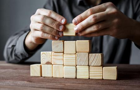 Uomo d'affari che costruisce una piramide con i cubi di legno vuoti. Concetto di gerarchia aziendale e strategia aziendale. Archivio Fotografico