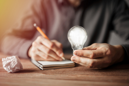Businessman holding light bulb and writing down in the notebook new creative ideas. Concept of innovative technology and creativity. Stockfoto