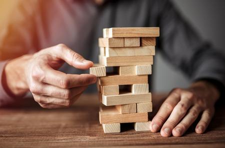 Geschäftsmann, der Holzklotz auf einen Turm setzt. Geschäftsplanung, alternative Risiko- und Vermögensstrategie im Geschäftskonzept,