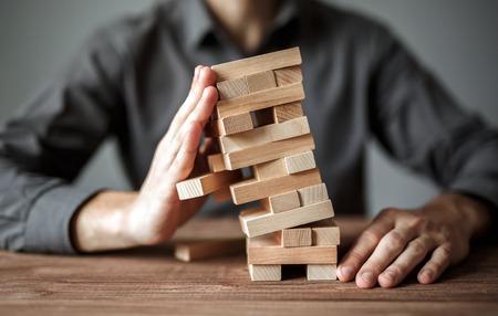 Geschäftsmann hält das Modell des Geschäfts, hergestellt aus Holzklötzen. Alternatives Risikokonzept, Geschäftsplan und Geschäftsstrategie. Versicherungskonzept.