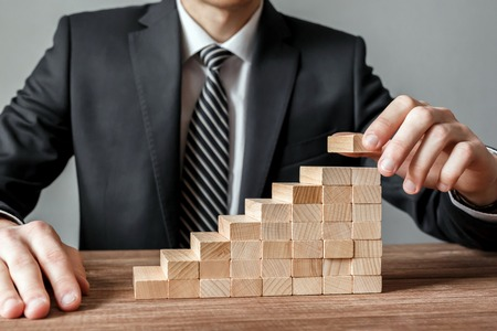 Businessman hand arranging stacking wooden blocks development as step stair Stockfoto