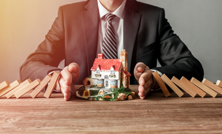 Close-up of a man stopping the wooden blocks from falling on house model. House insurance and security concept.