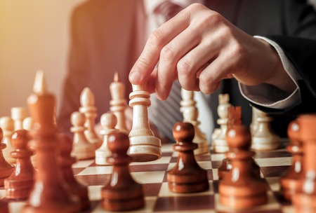 Hand of businessman moving chess figure in chess play. Strategy, management or leadership concept.