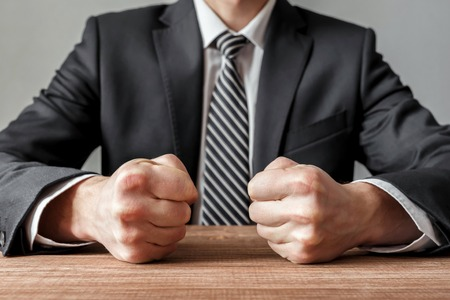 Angry businessman with closed fists on the table.