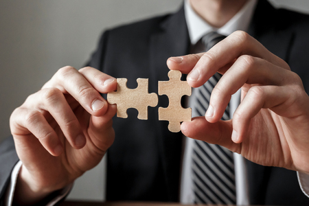 Businessman hand connecting jigsaw puzzle.Business solutions, success and strategy concept. Stockfoto