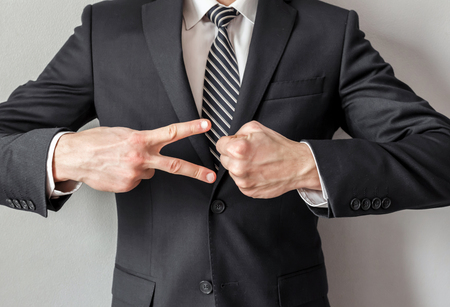 Businessman playing Rock, Paper, Scissors with himself,concept of way to make a decision.