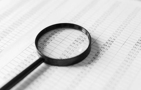 Financial reports and a magnifying glass with on table office.