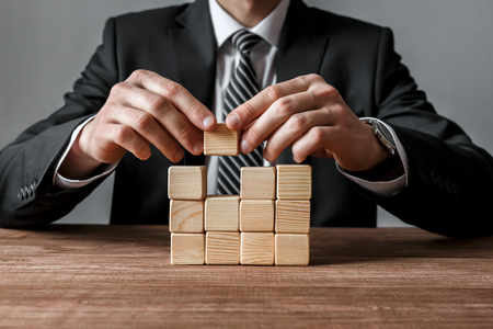 Closeup of businessman making a structure with wooden cubes