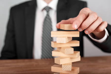 Businessman placing wooden block on a tower. Planning, risk and business strategy concepts.