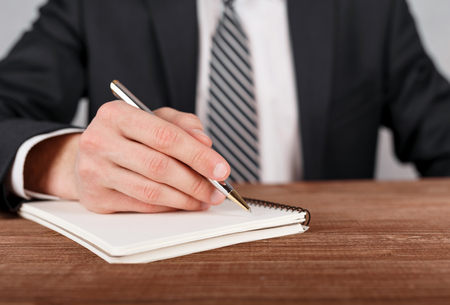 Close up of businessman in suit writing on notebook.