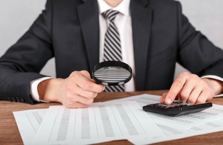 Businessman holding magnifying glass zoom and looking to financial statement