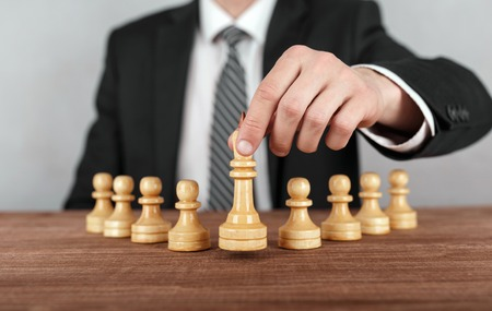 Businessman is moving chess figure of a king . Concept of business strategy.