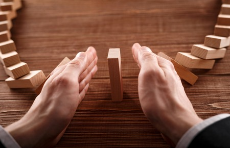 Close up of businessperson which is stopping group of dominoes from falling on the last domino.