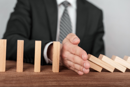 Businessman stopping domino effect with his hand. Security and insurance concept Stock Photo