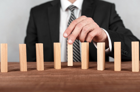 Businessman is placing wooden block in the center on a line of domino.Risk and business strategy concept.