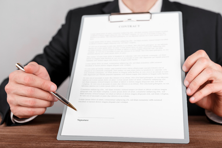 Businessman indicates the place for signing in the contract,which is attached to a clipboard. Stockfoto