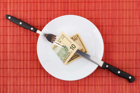 Money on plate with fork and knife. Business and financial concept