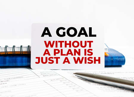 Business card with text A goal without a plan is just a wish lying on blue notebook. Banco de Imagens