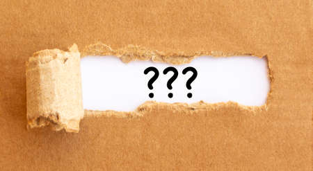 Questions appearing behind torn brown paper.
