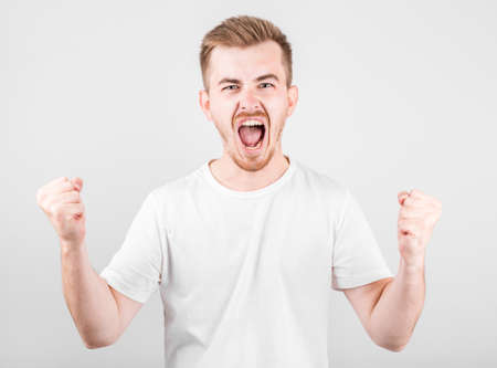 Young man celebrating victory over gray background. Stockfoto