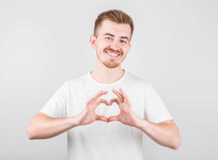 Portrait of smiling young man keeps hands on chest in heart shape sign, expresses sympathy Stockfoto